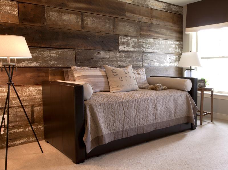 Tras el sofá, una pared de tablas de madera reciclada.