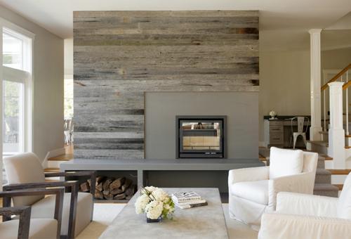 La pared de la chimenea, forrada con tablas de madera reciclada