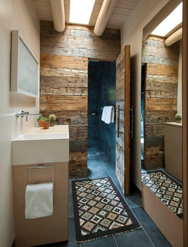 Una pared de madera reciclada, separa la ducha del baño