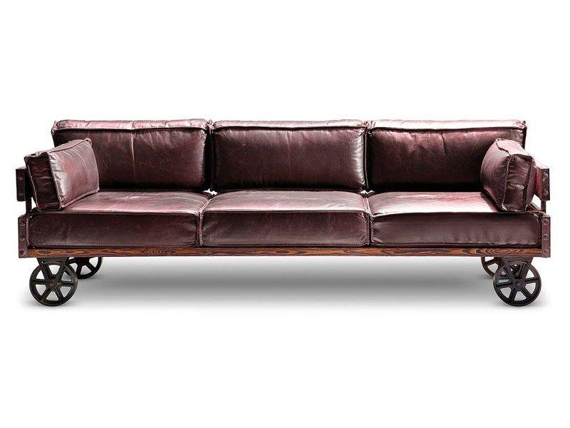Sofá de piel color marrón, con armazón de madera con ruedas, estilo industrial