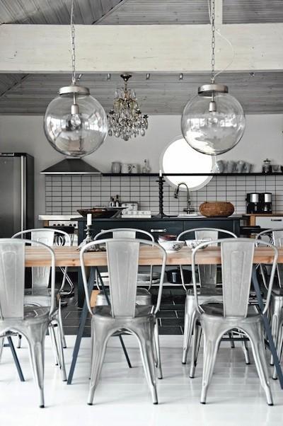 Sillas de metal apilables y mesa rústica.