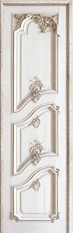 Una puerta con molduras y tallas barrocas.