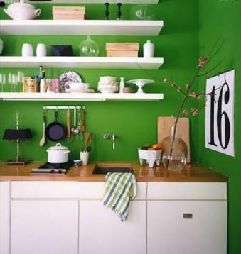 Paredes de color verde y cocina blanca.