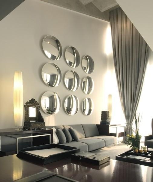 Nueve espejos convexos tras el sofá.
