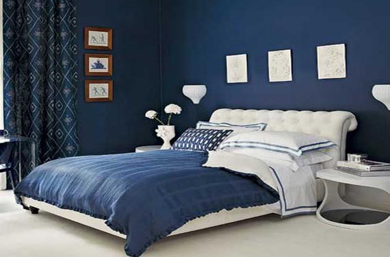 Amplio dormitorio pintado de color azul profundo.