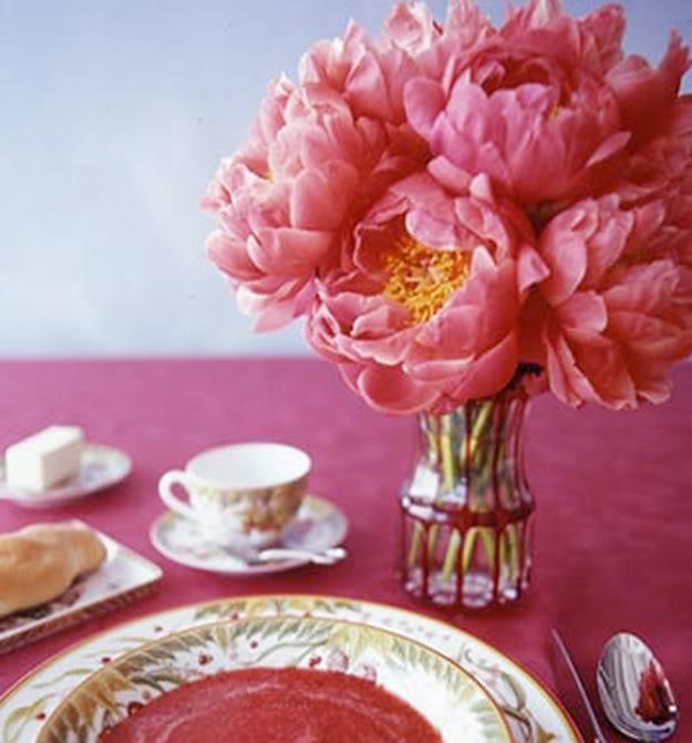 Mesa con peonias de fuerte color rosa.