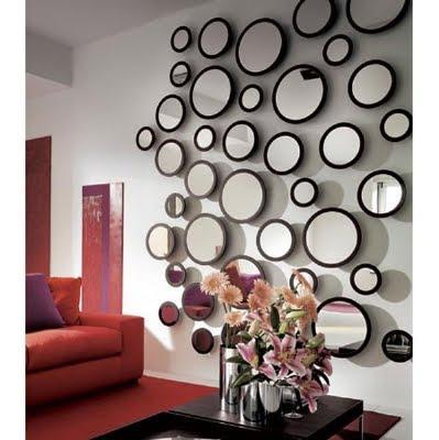 Pared cubierta de espejos circulares de distintos tamaños.