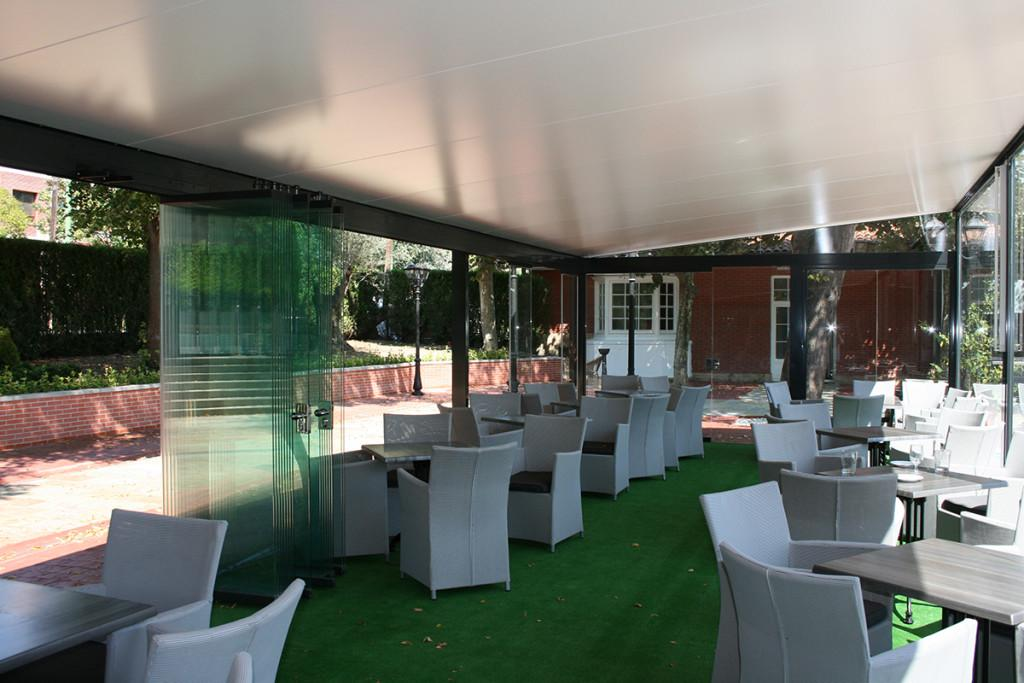 Restaurante con parte de las cortinas de cristal recogidas.