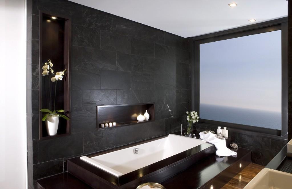 Las paredes de este moderno baño panelado de pizarra.