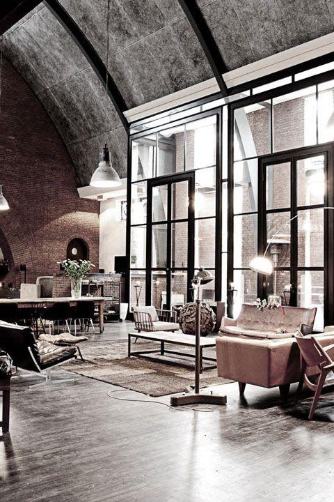 Vigas y ventanal de acero, techo de hormigón y suelo de cemento pulido.