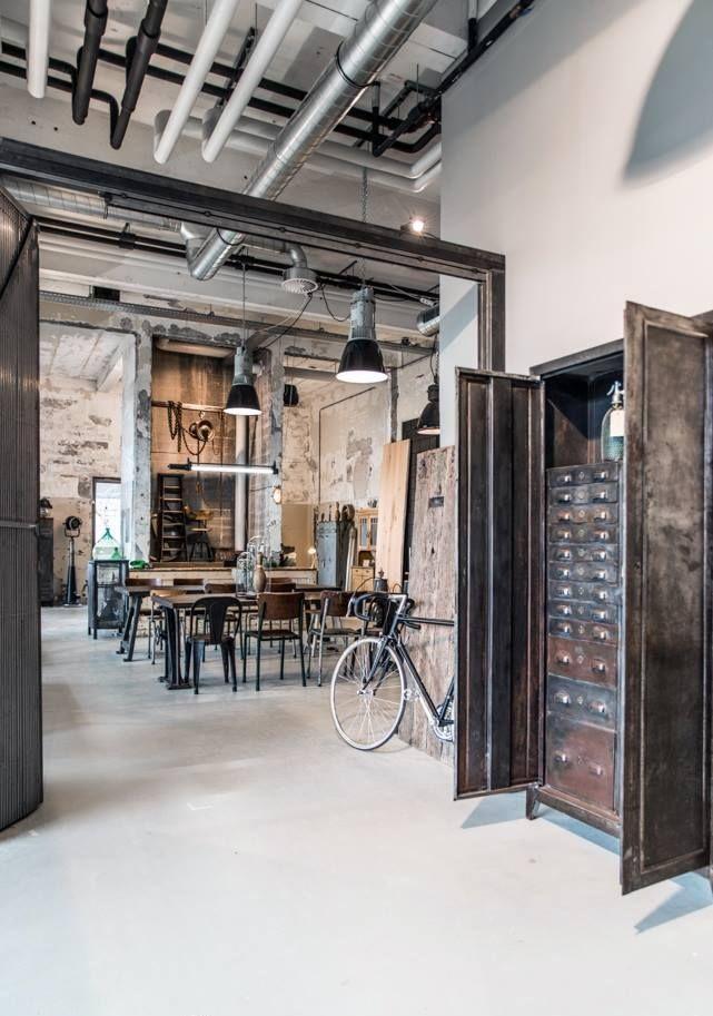 Tuberías visibles y mobiliario de madera y metal de estilo industrial.