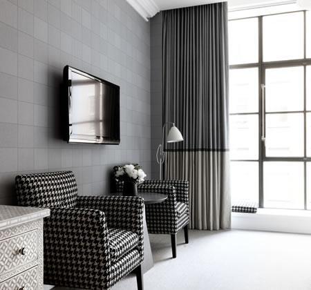 Dos butacones cubiertos con una tapicería de pata de gallo, en blanco y negro.