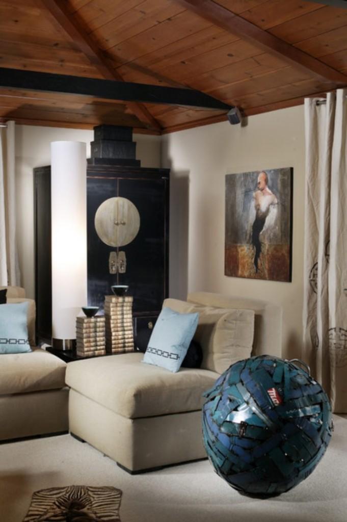 Un oleo y una pieza escultórica color turquesa en primer plano.