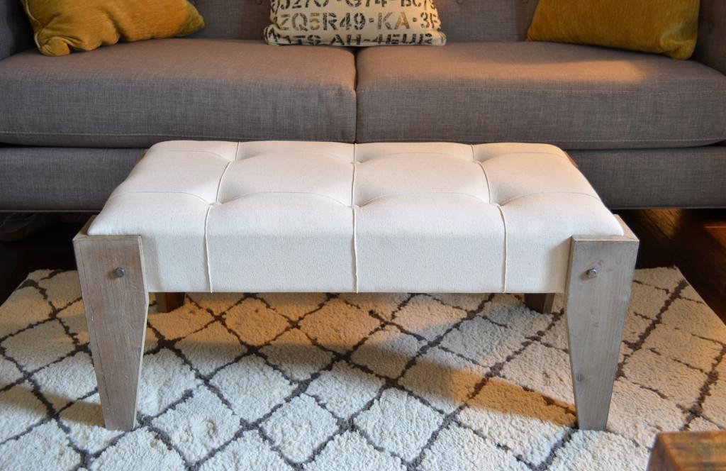 Un diseño rectangular fabricado en piel blanca y patas de madera lavada.