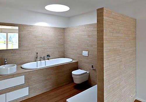 Un lucernário con forma redonda, ilumina este moderno cuarto de baño.