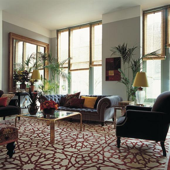 Una gran alfombra blanca con dibujos de celosías árabes en tonos burdeos.