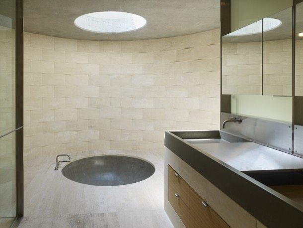 Un lucernario circular ilumina una bañera redonda de cemento pulido.