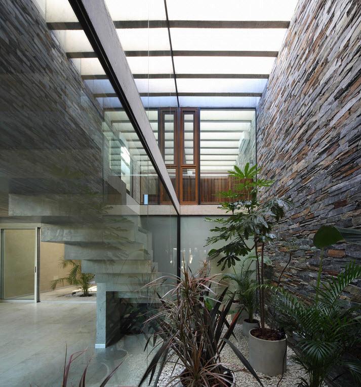 Una escalera y un patio interior iluminado por una gran claraboya.