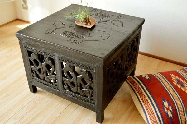 Una mesa auxiliar cuadrada de madera de estilo indonesio.