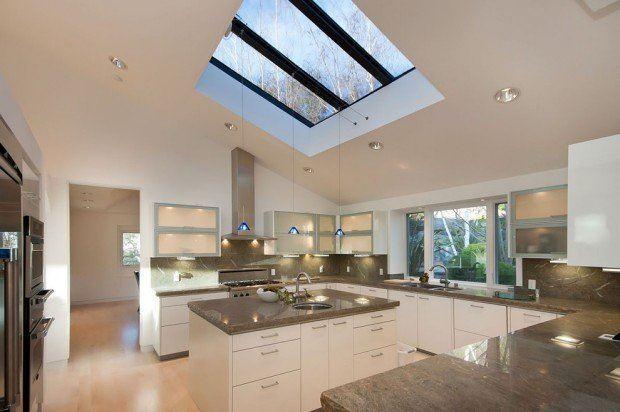 Una moderna cocina con un techo inclinado y en este una claraboya.
