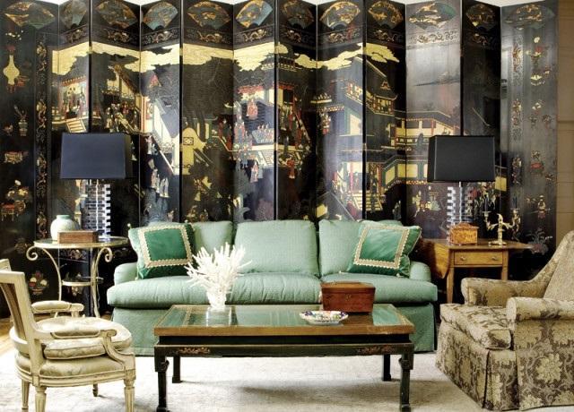 Un espectacular biombo chino como fondo tras el sofá.