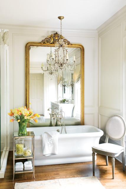 Un gran espejo clásico en pan de oro, centra la atención en el baño.