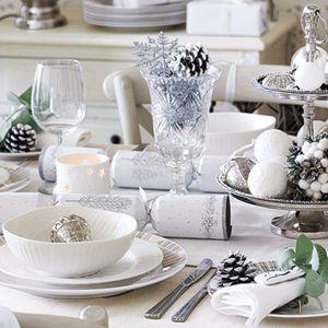 Mantel, servilletas y vajilla blanca copas de cristal tallado y tradicionales petardos en blanco y plata.