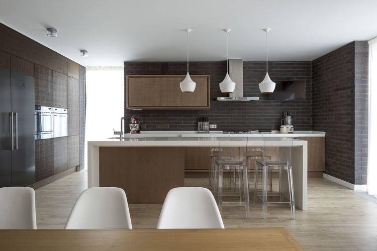 Paredes de ladrillos grises vistos y muebles modernos de madera y