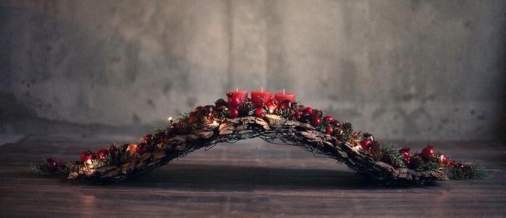 Pieza ornamental compuesta con ramas, corcho, velas y frutas, en tonos rojos.