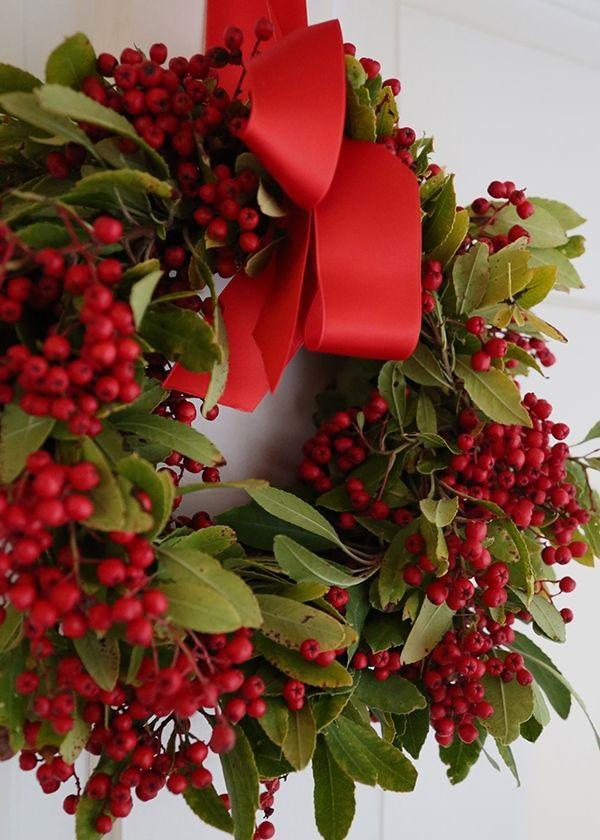 Una corona tradicional, es esta compuesta por bayas y lazo rojo, combinada con las verdes hojas de laurel.