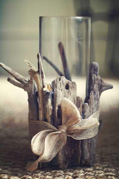 Un jarrón de cristal cilíndrico, con ramas secas alrededor y un lazo.