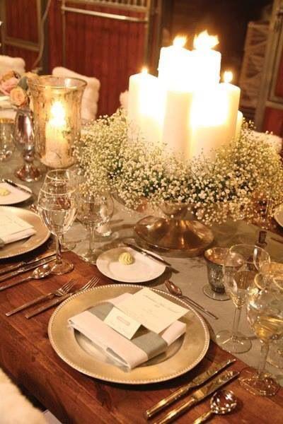 Con portavelas, bajoplatos y pie del centro de mesa en plata combinado con flores y velas blancas.