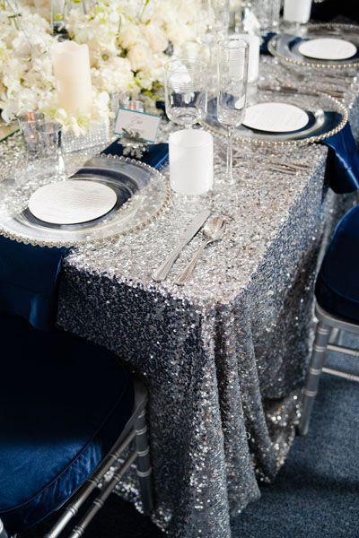 Mantel plateado, bajoplatos de cristal y centro de flores blancas.