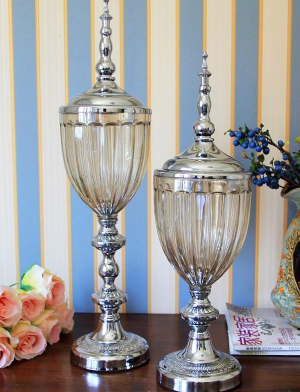 Bomboneras con el pie y la tapadera de metal plateado y la copa en cristal transparente.