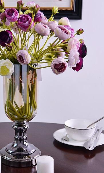 Un jarrón moderno, que combina el metal, en un tono plata ahumado y cristal transparente.