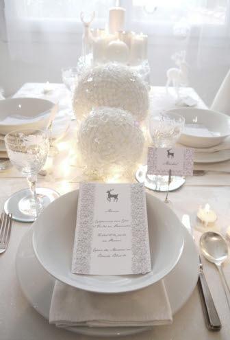 Mesa de navidad blanca, con  platillos para el pan y cubiertos  plateados.