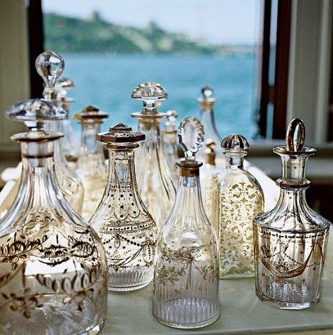Una colección de licoreras antiguas de cristal tallado, pintadas a mano.