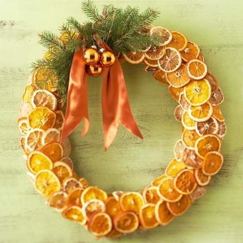 Corona de rodajas de naranjas secas, ramitas de pino,  bolas y  lazada en tono naranja.