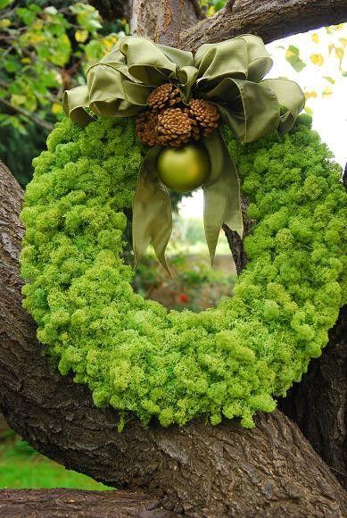 Un diseño realizado con musgo verde, una lazada, unas pequeñas piñas, y una bola.