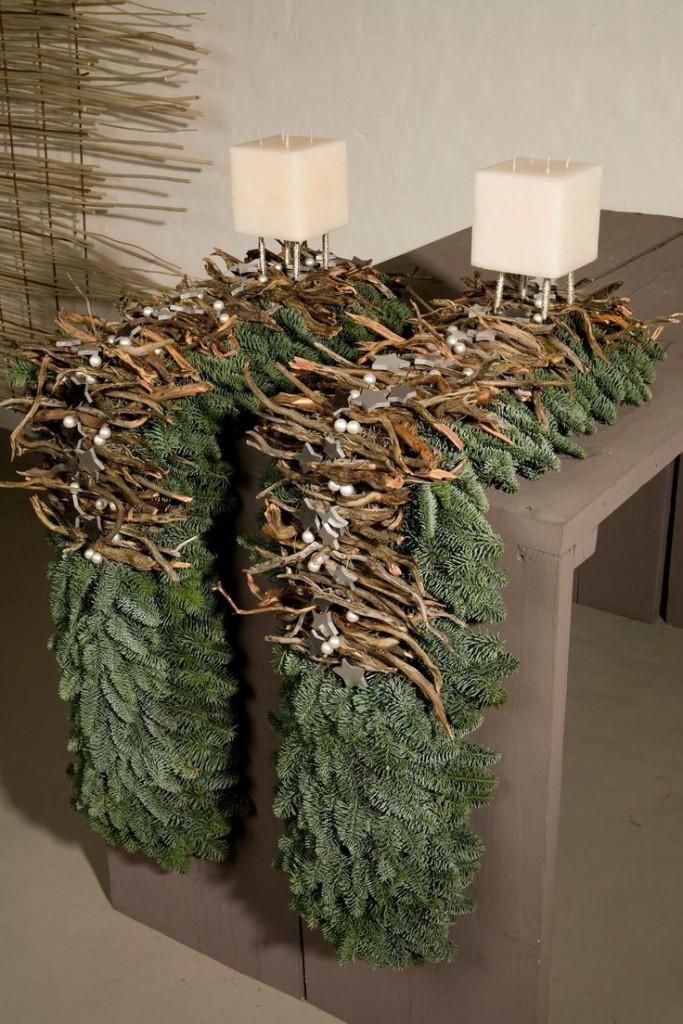 Centros de mesa formado por ramas de abeto, ramitas secas, bayas blancas y unas velas cuadradas también blancas.