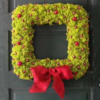Una corona cuadrada, con musgo,bolas de navidad rojas y una lazada roja.