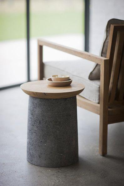 Una pieza cilíndrica de cemento, con otra redonda de madera sobre ella.