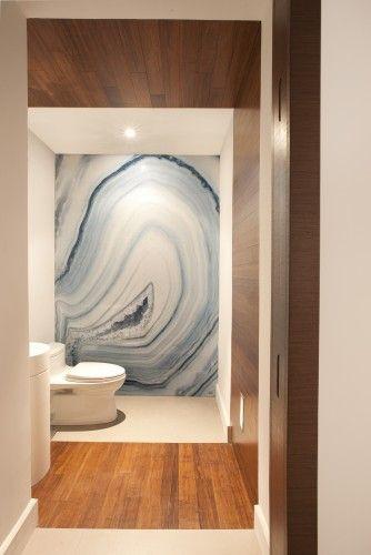 Una gran piedra de ágata,cubre una de las paredes del moderno baño.
