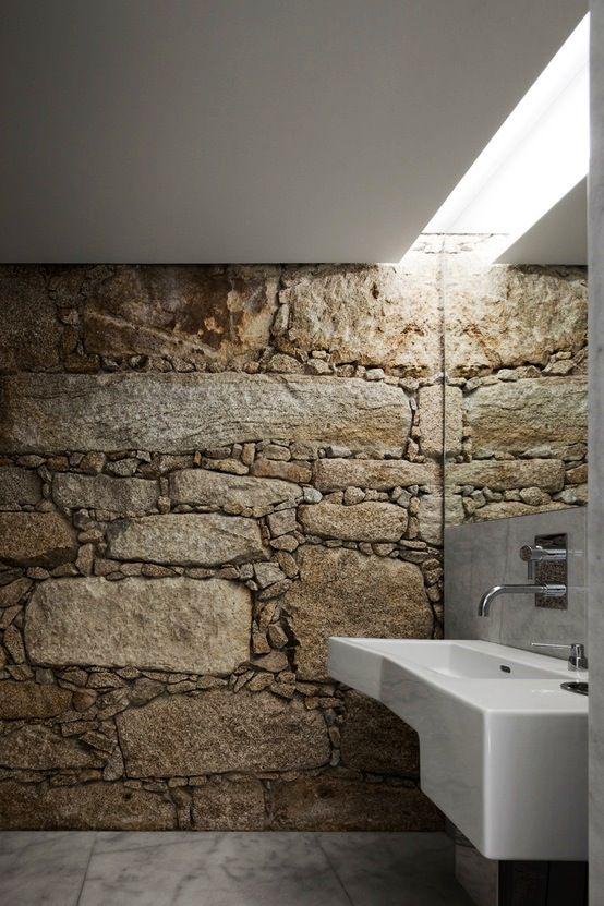 Un muro de piedra y una claraboya, como piezas clave del moderno baño.