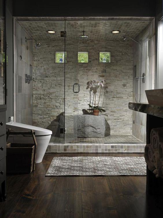 Pequeñas teselas, placas de mármol y piedra, recubren la ducha de este baño.