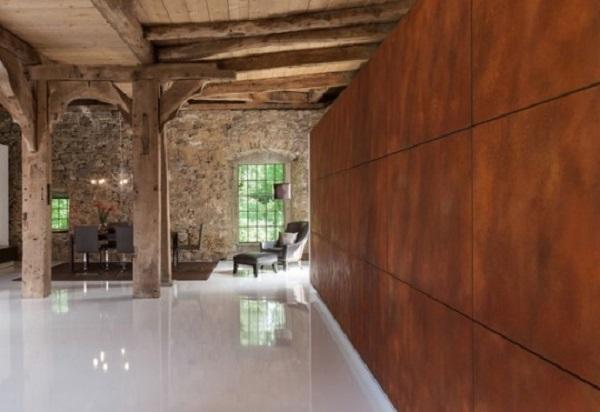 Acero cor-ten, en una de las paredes de esta habitación de estilo rústico.