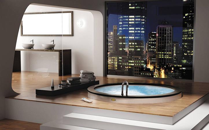 Una redonda bañera encastrada en el suelo junto a un gran ventanal.