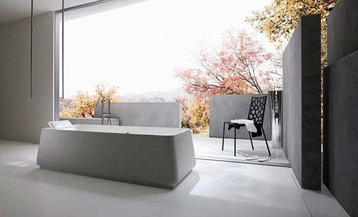 Un baño de estilo minimalista, con muros de hormigón  y una bañera trapezoidal.