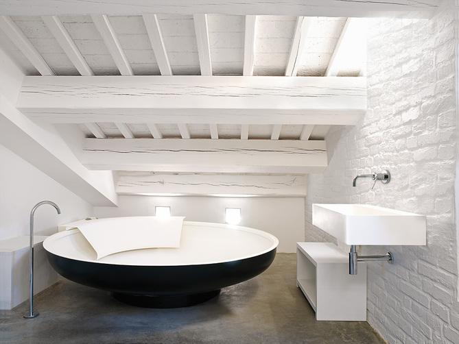 Un  cuarto de baño de estilo rústico con una moderna  bañera Ufo y grifería Fez, de marcado estilo minimalista.