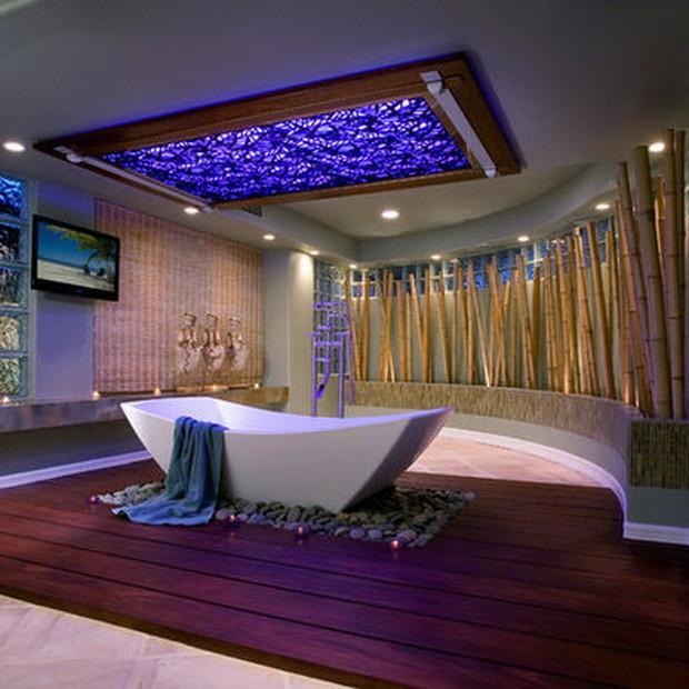 Con un separador curvo de cañas de bambú y una bañera sobre un suelo de madera y cantos de río.
